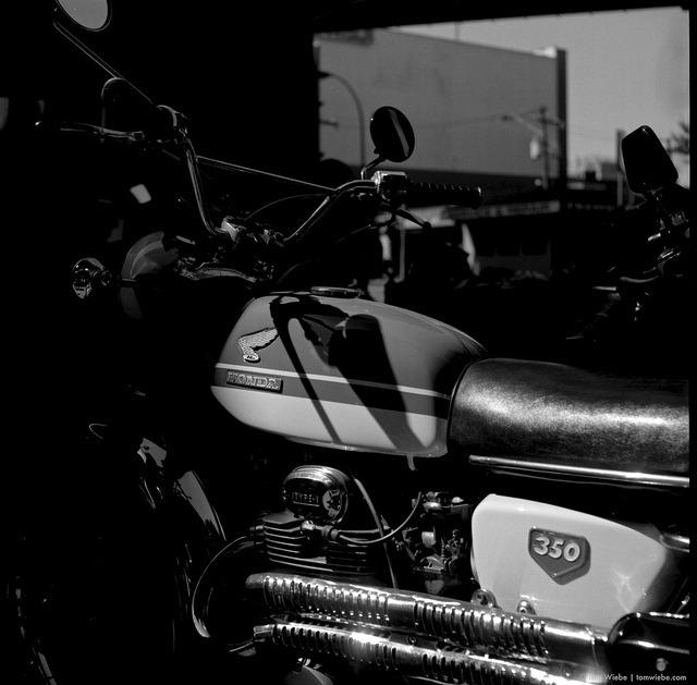 Honda 350 on Flickr.Via Flickr: My buddy Pete gave me a couple rolls of T-Max 100 recently, having decided to stick to colour shooting. I haven't shot T-Max in nearly 20 years. Always had a love/hate relationship with the film. I'm pleased to announce that my love/hate relationship with T-Max continues. It's just spiffy when everything comes together. Remarkable, even but, given that I'm shooting with a 64 year old Rolleiflex, well, the precise exposure required for the best results from T-Max just ain't gonna happen. Both rolls shot, a couple of successes and a bunch of middling, muddling blech. I'll stick to my more forgiving old school favourites, Tri-X and the like. I like this old Honda though, shot near the entrance to Granville Island.
