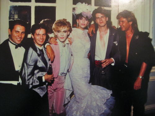 johntaylordaily:  Nick & Julie Anne got married 27 years ago today…  Simon seems to be missing a shirt… and really I have no problem with that.