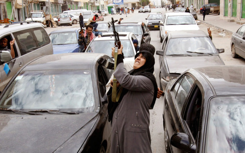 A Libyan woman firing her AK-47 into the air in support of Libyan rebels upon hearing the news that rebel forces took control of the city of Benghazi from Gadhafi-Loyalist troops. Libya - March 19, 2011