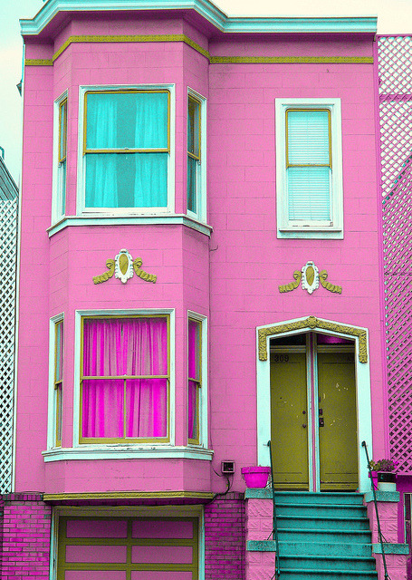 (image description: a digital photograph of a bright pink brick two storey house in san francisco taken by christopher lynch. it has mustard coloured doors and details around the trim, with some turquoise steps and curtains.) this is the dream house i would buy as a wedding present for majestic legay and jessica if i had the funds to be a properly decadent sugar mama.