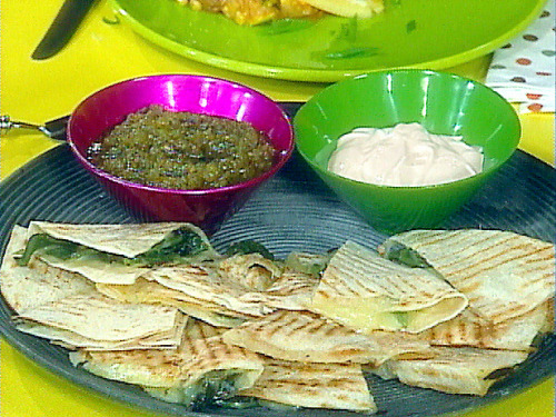 omomnom:  Grilled Green Chili Quesadillas Ingredients 3 fresh chile peppers, such as poblanos — any variety may be used, according to your tolerance for heat 4 (12-inch) large flour tortillas 3 cups (3/4 pound brick) smoked cheddar (recommended: Cabot brand, shredded) 1 cup store bought salsa verde, available on chip and snack aisle or in Mexican food section 1 cup sour cream 2 tablespoons chopped fresh cilantro leaves Directions Heat a grill pan over high heat. Place whole chiles on grill and char all over. about 10 minutes. Remove from heat and split chiles. Scrape away seeds with a spoon and slice. Heat a large nonstick skillet or griddle over medium high heat. Char the tortilla and blister it on 1 side, 20 seconds, then flip tortilla. Cover half of the tortilla with cheese and chilies, then fold over. Press down gently with spatula. Cook quesadilla 15 seconds more on each side, transfer to a cutting board. Repeat. Pile up 2 completed quesadillas at a time and cut into 3 generous wedges. The yield will be 12 pieces from 4 quesadillas. Serve slices on a large platter with small dishes of salsa verde and sour cream for topping. Garnish the platter and toppings with chopped cilantro.