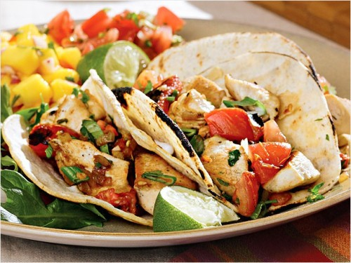 Chicken Tacos with Charred Tomatoes  2 plum tomatoes, cored 		 1 clove garlic, minced 8 ounces boneless, skinless chicken breast, trimmed of fat 		 1 small jalapeno pepper, seeded and minced 1/4 teaspoon salt 		 2 teaspoons lime juice, plus lime wedges for garnish 1/8 teaspoon freshly ground pepper 		 2 teaspoons chopped fresh cilantro 2 teaspoons canola oil, divided 		 2 scallions, chopped 1/2 cup finely chopped white onion 		 6 small corn tortillas, heated  Heat a medium skillet over high heat until very hot. Add tomatoes and cook, turning occasionally with tongs, until charred on all sides, 8 to 10 minutes. Transfer to a plate to cool slightly. Cut the tomatoes in half crosswise; squeeze to discard seeds and chop the remaining pulp and skin.  Cut chicken into 1-inch chunks; sprinkle with salt and pepper. Add 1 teaspoon oil to the pan and heat over high heat until very hot. Add the chicken and cook, stirring occasionally, until it is browned and no longer pink in the middle, 3 to 5 minutes. Transfer to a plate.  Reduce the heat to medium and add the remaining 1 teaspoon oil. Add onion and cook, stirring, until softened, about 2 minutes. Add garlic and jalapeño and cook, stirring, until fragrant, about 30 seconds. Add lime juice, the chicken and tomatoes. Cook, stirring, until heated through, 1 to 2 minutes. Stir in cilantro and scallions. Divide the chicken mixture among tortillas. Serve with lime wedges.
