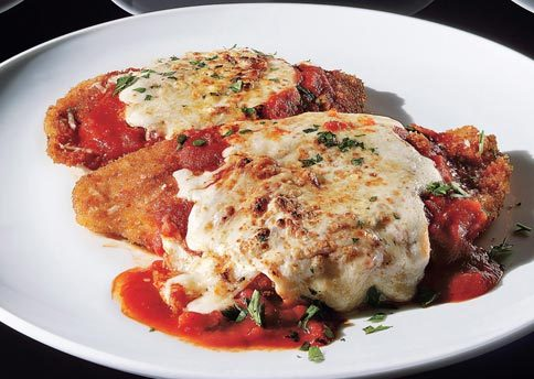 "Chicken Parmesan  You'll Need: 4 boneless, skinless chicken breast halves (4-6 oz each) 1/2 tsp salt 1/2 tsp black pepper 2 egg whites, lightly beaten 1 cup bread crumbs, preferably panko 2 Tbsp grated Parmesan 1/2 Tbsp dried Italian seasoning 1 Tbsp olive oil 1 cup tomato sauce (we love anything from Muir Glen) 4 oz shredded part-skim mozzarella Fresh basil leaves (optional)  How to Make It: Preheat the broiler. Cover the chicken breasts with parchment paper or plastic wrap and, using a meat mallet or a heavy-bottomed pan, pound the chicken until it is uniformly 1/4"" thick. Season with the salt and pepper.  Place the egg whites in a shallow bowl. Mix the bread crumbs, Parmesan, and Italian seasoning on a large plate.  Dip each breast into the egg whites to coat both sides and then into the crumb mixture, patting the crumbs so they fully cover the chicken.  Heat the oil in a large skillet or saute pan over medium heat. Cook the chicken for 3 to 4 minutes on the first side before turning. (The crust should be deeply browned and crunchy.) Cook for another 2 to 3 minutes, then transfer the chicken to a baking sheet.  Spoon the tomato sauce over the chicken pieces, then top with the cheese and place underneath the broiler for 2 to 3 minutes or until the cheese is fully melted and bubbling. Serve garnished with basil (if using)."