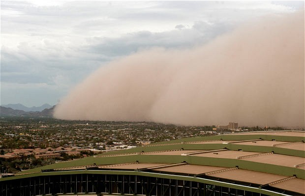 "inothernews:  BLOWN AWAY    A dust storm, known as a ""haboob,"" moves across Phoenix, Arizona about 6pm Thursday, dramatically reducing  visibility and enveloping residents in an eerie, rust-coloured glow.  It's the third major dust storm that has hit the Phoenix metropolitan  area since July 5; ""microbursts"" of wind, gusting up to 60 miles per hour, caused much of the area damage.  (Photo: Pat Shannahan / The Arizona Republic via the AP / The Telegraph)"