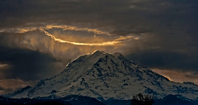 "jtotheizzoe:  Photographer snaps heavenly photo of Mt. Rainier The weather phenomenon behind the beauty: ""The skies were mostly overcast that morning, but it looks like air flowing over Mt. Rainier created some localized turbulence that opened up a small hole in the sky.   When air gets turbulent, it can rise and sink. Sinking air dries as it does so, and create holes in the clouds."" (via KOMO News 