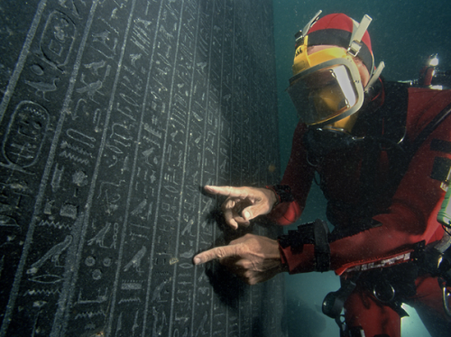 "dwellerinthelibrary:  ""A diver deciphers a stele from King Nectanebo I, found at the site of Heracleion."""