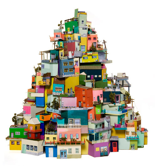Mexican-American artist Ana Serrano is fascinated by the seemingly random evolution of cities, constantly made, unmade and re-made by tenants, residents and generations.  Her piece Cartonlandia, made of cardboard boxes is inspired by the sights, color combinations and reandomness of her morning walks in L.A. and in by the structures of Brazil's favelas.  More info linked above.