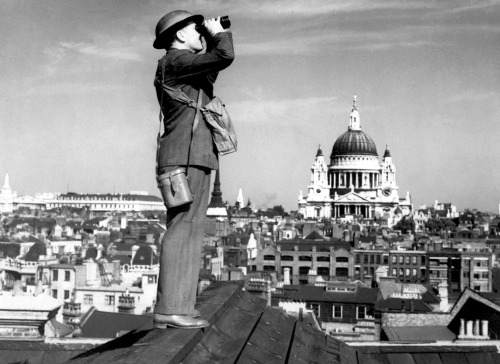 A British plane spotter on a rooftop in London on the lookout for German airplanes during the Blitz.   The building featured prominently in the background is St Paul's Cathedral.