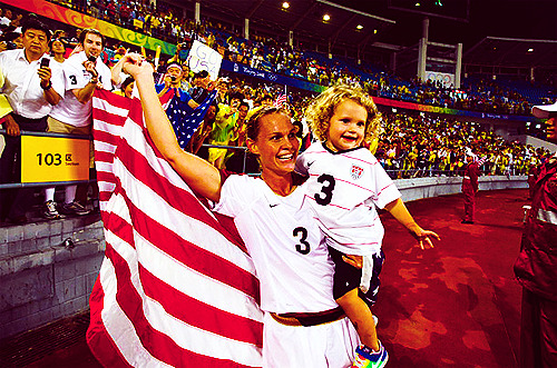 Christie Rampone of the US women's soccer team hoists the flag and her daughter Rylie Cate after the American women defeated Brazil in the final.