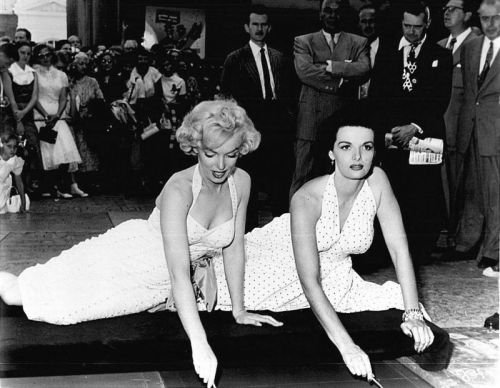 "June 26, 1953: Marilyn Monroe and Jane Russell writing their names in the cement outside the Grauman's Chinese Theatre. As a child, Marilyn had often tried to place her hands and feet in the hand prints and foot prints of the previous movies stars who have left their place outside Grauman's Chinese Theatre. Movie stars like Jean Harlow who was one of Marilyn's favourite actress'. ""I could never find my size foot, they were always too big"", Marilyn once said."