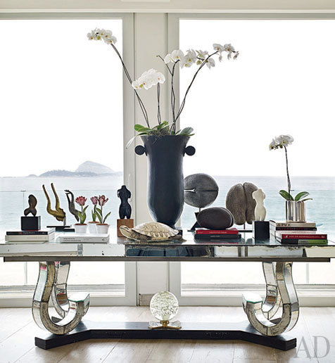 Overlooking the Cagarras archipelago, a Marcel Coard table hosts an  ivory turtle, an Art Deco vase, and sculptural coco de mer seeds.