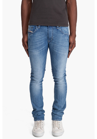 Thavar 8w7 by Diesel. Skinny jeans with low rise in faded blue denim. Moderately distressed five pocket styling. Logo flag at coin pocket. Dark copper tone logo rivets at front. Signature logo stitching and grey stitch detail at rear. Worn leather logo patch at back rear. Whiskering at thighs and back knees. Creasing at thighs. Sanding at front and rear. Contrast stitching in beige. Zip fly.More…