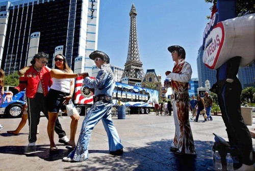 Turning the sidewalk into a stage:  Street performers on the Strip jostle for space with promoters, peddlers and pedestrians. County officials recently announced a plan to tame the space, but for now, it's anyone's game. Photo:  Michael Jackson impersonator Chris Gardener and Elvis impersonator Tony Gallardo ply their trade with a tourist while Elvis impersonator Robrigo Gonzalez, right, watches. Credit: Genaro Molina / Los Angeles Times