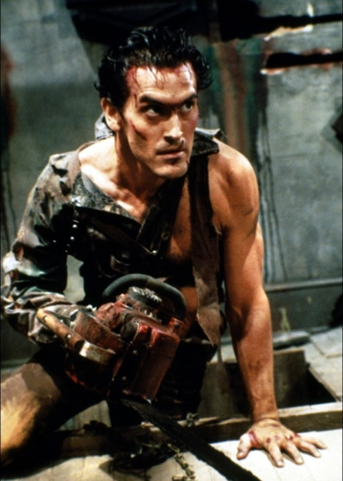 beautyandterrordance:  Bruce Campbell as Ash Williams, in Evil Dead II: Dead By Dawn. A glove belonging to the A Nightmare on Elm Street Freddy Krueger character can be seen hanging above the door of the Toolshed when Ash carves his girlfriends head with a chainsaw and when he's looking for the pages in the later cellar scenes. This was in response to the use of The Evil Dead on a television screen in A Nightmare on Elm Street. (via)