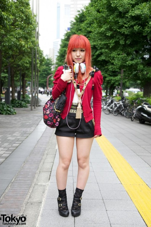 Meet Mina, a 19-year-old university student. Her bright orange/red  hair and stylish fashion caught our attention right away when we spotted  her on the street in the Shinjuku area of Tokyo. Mina's is a big fan of the Japanese fashion brand Murua (produced by  Momoko Ogihara) and her outfit reflects that. Her red cardigan, cute  black shorts, huge tassel necklace (showing influence from previous  Dolly Kei trends), and double-buckle platform heels are all from Murua.  Her non-Murua accessories include Fostex headphones, a Betsey Johnson  Betseyville purse, and an Apple iPhone with a Rilakkuma case. Mina told us that her favorite fashion brand is Murua (surprise!) and  her favorite shop is GR8 Harajuku. Her favorite musical artists include  Verbal and Takkyu Ishino