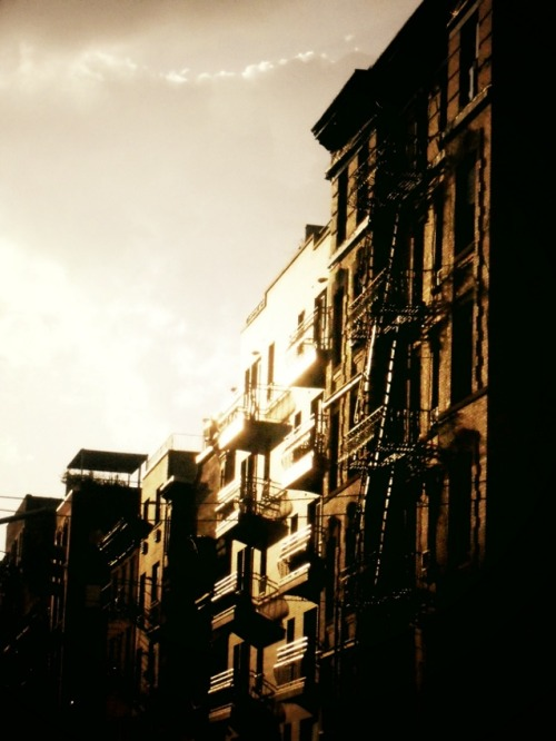 "nythroughthelens:  ""When the sun hits"". Lower East Side, New York City. It's been exactly a year since I moved from the border area of Spanish Harlem in Upper Manhattan down to the Lower East Side. This photo will forever remind me of what a turning point this move was for me. My life has changed in so many ways since I moved that it feels as if my life has been divided in two parts now; life before moving to the Lower East Side and life after moving to the Lower East Side. Having been notified that I had to find an apartment in a period of only two weeks because of a not-so-great landlord issue I spent every waking moment scouring Manhattan for a new, affordable apartment (a rarity). New York City was experiencing a dramatic heat wave at the time with temperatures in the triple digits and humidity at nearly 100 percent for days on end. On a 100 degree + (Fahrenheit) weekend, I moved into a tenement on the Lower East Side. This was no easy feat considering that my new apartment was on the 5th floor of a walk-up (it's 76 steps up to my apartment! I have grown to love it). With no air conditioner, no fans, no internet and two extremely angry cats, I experienced the heat wave in all its glory. I spent that memorable weekend roaming the nearby streets taking photos between ducking into places hoping to catch some relief. I would spend the rest of my time laying out ice blankets and pans of ice water for my cats because the temperature in the apartment was close to 120 degrees Fahrenheit. In the middle of my first week living on the Lower East Side, I decided to take a two hour tour at the Tenement Museum.  Since my apartment is one of the early tenements and I am an avid New York City history buff, I couldn't resist finally going to this museum. To say that it was one of the most incredible experiences I have had would be an understatement. Being the daughter of an immigrant to the United States (my mother came here as a concentration camp survivor of WWII when she was nearly 10 years old) and growing up in the dense cultural center of Flushing, Queens (a borough of New York City), I have always enjoyed learning about other people's experiences with immigration to New York City and the United States. On our tour that day, we learned all about the families who lived in the tenement apartments we toured (kept as they would have looked like when the families lived there) and viewed census records, photographs and keepsakes. At one point we listened to a short oratory recollection by an inhabitant of one of the apartments via a recording. She spoke about what it was like to live in the tenement we were standing in during the beginning of the 20th century.   Being able to visually see these recollected remnants of someone's experiences as they described them was a special experience. My group was also taken through a non-restored apartment in various stages of decay. Writing etched into crumbling walls indicated the amount of garments that had been stored in the room by tenants who would often share these tiny dwellings with their large families. Every object, every garment meant so much to them. Since it was the two hour tour, we were able to ask a lot of questions of the historians and engage in quite a bit of spirited discussion. At the end of our tour through the early tenements, we spent a good half hour around a table in a cooled room eating cookies and drinking iced tea while listening to each other's family histories. We cried and laughed together and when it was all over we hugged each other as if we had become a family right then and there. It was a quintessential New York City experience. This photo for me represents the heat of that summer, the heat in my apartment that was similar to the heat felt by the tenants over one hundred years ago before there was air conditioning/reliable fans and many of the amenities we are used to in our modern living environments. It represents the heat of the hot tears that ran down my face while I cooled off that one morning at the Tenement Museum after sharing my own family's history and listening to other people's family's immigration stories. The sun hit the buildings in the most beautiful of ways that summer. The sun hits the buildings in the most beautiful of ways all year here. Because the Lower East Side is home to many of the original tenements which are shorter than modern buildings, it's one of the neighborhoods where the sun can be seen regularly as it illuminates the fire escapes on the tenements that housed early New York City residents who carried with them many of the same hopes and dreams as those who inhabitant the same tenements today. I wouldn't trade the light and the heat for anything. —- View this photo larger and on black on my Google Plus page —- Buy ""When the Sun Hits - Lower East Side"" Posters and Prints here, View my store, email me, or ask for help."