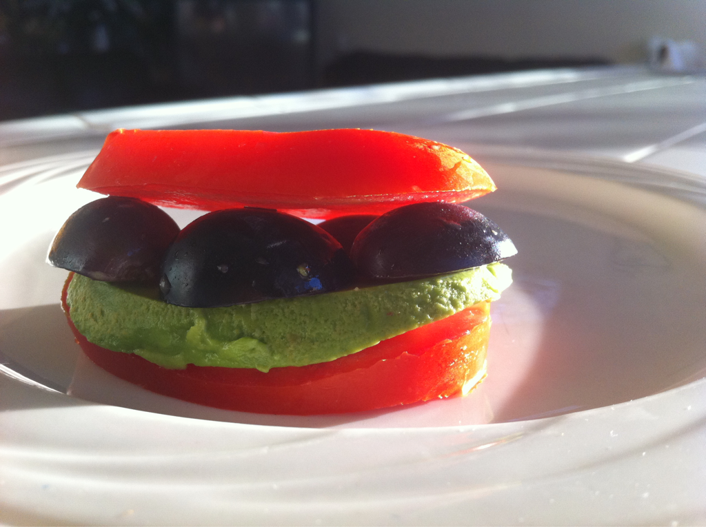 Tomato sandwich with avocado patty and grape halves. It tastes very daring yet delicious.