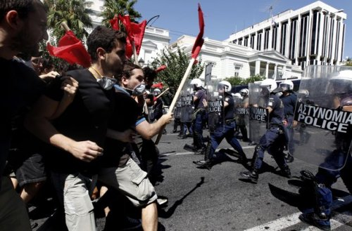 Protesting students clash with riot police in central Athens, Wednesday, Aug. 24, 2011, during a demonstration against new legislation on reforming university education. Some 1,000 students took part in the protest. No arrests or injuries were reported. The new law, which was approved by the Greek parliament Wednesday, will reduce the power of student political unions in universities and make it easier for police to enter university grounds until now protected by strict asylum laws. (AP Photo/Petros Giannakouris)
