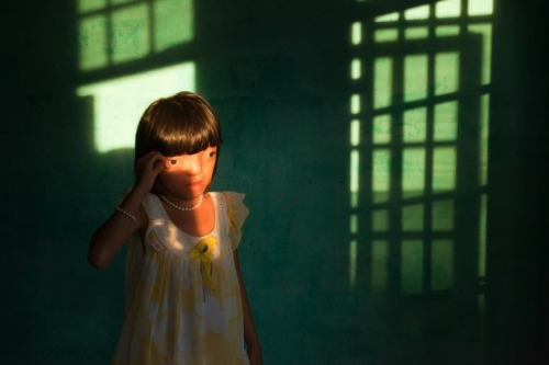 "Nguyen Thi Li, aged 9, who lives in the Ngu Hanh Son district of Da Nang in Vietnam, suffers from disabilities believed to be caused by the defoliating chemical Agent Orange. During the Vietnam War, US forces sprayed Agent Orange over forests and farmland in an attempt to deprive Viet Cong guerrillas of cover and food. The dioxin compound used in the defoliant is a long-acting toxin that can be passed down genetically, so it is still having an impact forty years on. The Vietnam Red Cross estimates that some 150,000 Vietnamese children are disabled owing to their parents' exposure to the dioxin. Symptoms range from diabetes and heart disease to physical and learning disabilities. Ed Kashi speaks about the project:""I was in Danang, Vietnam to work on a short film about child victims of Agent Orange and, while shooting video, was confronted with this incredible moment where the light, composition, character and mood combined to present something magical, transcendent and ultimately beautiful in its essence. Yet, it also showed the ongoing effects of a war that ended 35 years ago. Nguyen Thi Ly, a 9 year old girl afflicted with the genetic defects associated with Agent Orange exposure, represents yet another generation of children in Vietnam who need care and support."""
