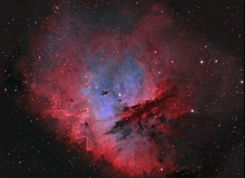 From Astronomy Picture Of The Day; August 25, 2011:  Portrait of NGC 281  J-P Metsävainio (Astro Anarchy)   Look through the cosmic cloud cataloged as NGC 281 and it's almost easy to miss stars of open cluster IC 1590.  But, formed within the nebula, that cluster's young, massive stars ultimately power the pervasive nebular glow.  The eye-catching shapes looming in this portrait of NGC 281 are sculpted columns and dense dust globules seen in silhouette, eroded by intense, energetic winds and radiation from the hot cluster stars.  If they survive long enough, the dusty structures could also be sites of future star formation.  Playfully called the Pacman Nebula because of its overall shape, NGC 281 is about 10,000 light-years away in the constellation Cassiopeia.  This composite image was made through narrow-band filters, but combines emission from the nebula's hydrogen, sulfur, and oxygen atoms in a visible spectrum palette.  It spans over 80 light-years at the estimated distance of NGC 281.