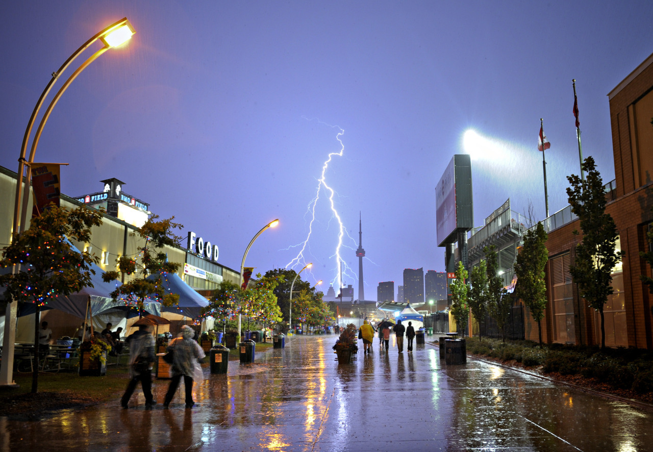 Photos of the dayCanadian National Exhibition (CNE) goers run to take cover from the rain as a massive storm hits Toronto, Wednesday evening, August 24, 2011. (Aaron Lynett/National Post)