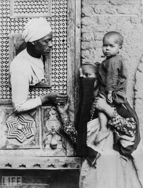 life:  From deep in LIFE.com's archives, some of the earliest photos of Egypt…  Pictured: An Egyptian man leans through a small ornate window to hold his wife's hand.