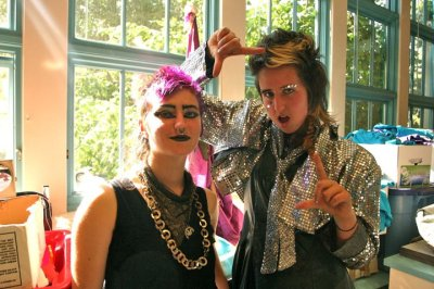 [Image: two people wearing sequined outfits, lots of makeup, and sparkly jewelry posing for the camera.] Two transfabulous, genderqueer kids glammin it up in drag workshop at Queer Rock Camp.