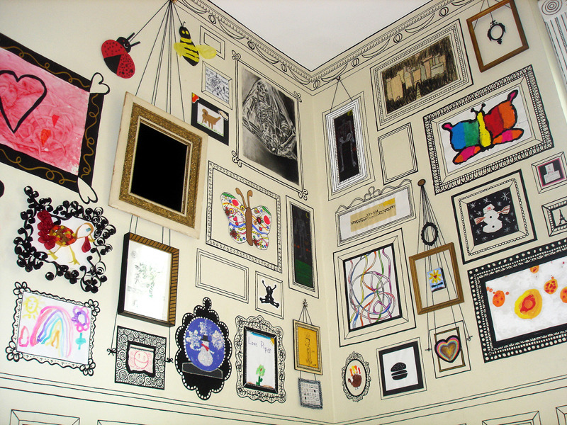 """These walls, covered in hand drawn frames and moldings, are WTF incredible. The artist hung some of her children's art, painted the frames with black craft paint, and used Sharpies to do the detail work. I desperately want this done in my office!"""