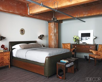 In the bedroom, Volpe designed the sconces and bed, which is upholstered in a Rose Tarlow leather and dressed with Pratesi linens; the bedside cabinet and  armchairs are by Frits Henningsen, the 1950s commode is by Jacques  Adnet, the mirror is by Line Vautrin, and the photograph is by Hiroshi  Sugimoto. Photographer: William Abranowicz