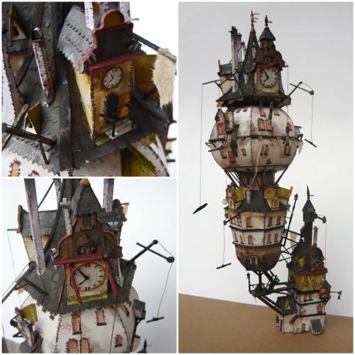 bookspaperscissors:  Clock Tower Here's my latest model. It took about 3 months to build it, like the other ones. It's in a 1:200 scale and is made of a 200g/m2 paper. I painted it with watercolour. It was quite hard to get it to balance, that's why I put a small stone in the lower building. There was a lot of work with it…a lot. raskolnikov0610