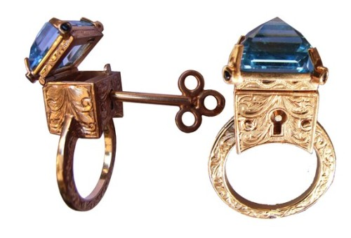 "ghoulnextdoor:  Friday Fripperies 9ct Yellow Gold Engraved Topaz Locking Poison Ring with Key on Chain by MetalCoutureJewelry ""This magnificent poison ring features a large central topaz stone that  can be unlocked with a key to reveal a tiny secret compartment. The  whole ring is covered in decorative engravings, and on each of the fours  claws holding the topaz there are tiny bezel set blue sapphires (we can  alternate the sapphires for diamonds if you wish, just let us know in  the notes to seller section).  It has been entirely hand made (including  the locking mechanisms). The dimensions of the locking box are approx  12mm wide x 12mm deep x 18mm from the top of the topaz to the bottom of  the box. The key to open it is approx 23mm long, and comes on a 50cm  chain to be worn around the neck."" $3500"