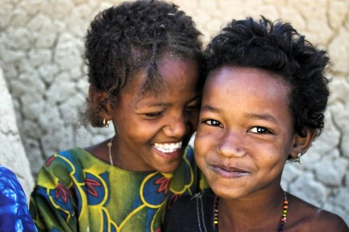 "That's what I call a smile, Menaka, northern Mali  ""These two absolutely lovely girls were two of a billion kids in a Bella family I interviewed outside of Menaka, in northern Mali. They are standing right by the family's small granary for fonio, a tiny kind of millet, which they collect by hand where it grows wild. Fonio is one of the most important cereals in West Africa, and I believe all the way across the continent to Sudan and Ethiopia. The grains are tiny, tiny, and people spend enormous amounts of time first collecting, and then removing the husk. This family would generally eat a meal consisting mainly of fonio per day, to try to make it through to the next harvesting season without having to purchase grains."" By Emilia Tjernström"