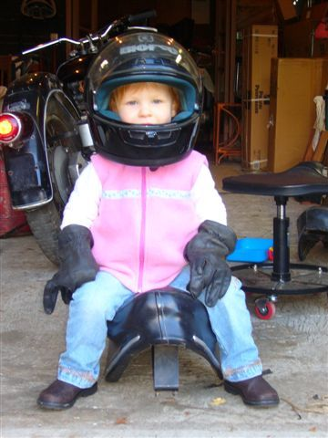 Here is a picture of my daughter when she was about 3 yrs old helping out in the garage. She is now 6 yrs old and rides with me on my 1968 R50US BMW. I wrote a little blog post wondering how we might influence our children as a rider and owner of vintage motorcycles. I am happy that my oldest wants to ride, and my younger daughter at 4 yrs old is looking forward when she can reach the passenger pegs.   Aww, a little MotoLady in the making! :)  (Submission from Brian B.)