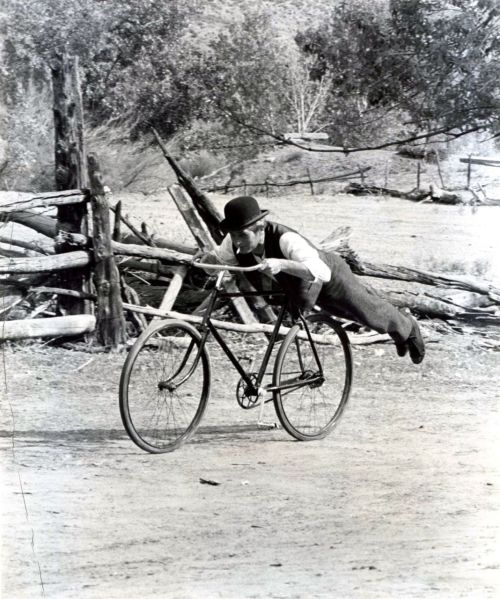 Paul Newman rides a bike. On his belly.