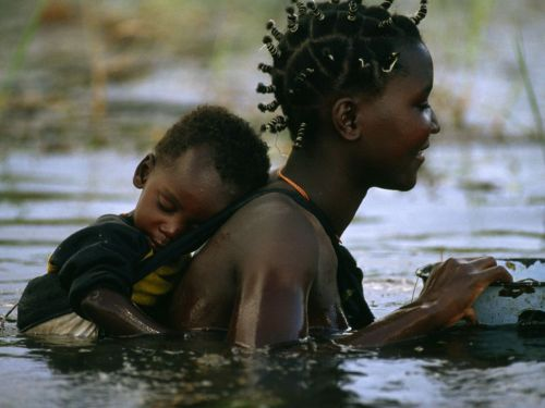 "Mbukushu Mother and Child, Okavango River, Botswana ""A Mbukushu mother and child cross Botswana's Okavango River, whose seasonal floods bring life to a parched land."" By: Frans Lanting"