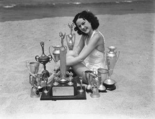 """Miss California Bathing Beauty"" and her trophies at Venice Beach, CA - 1936"