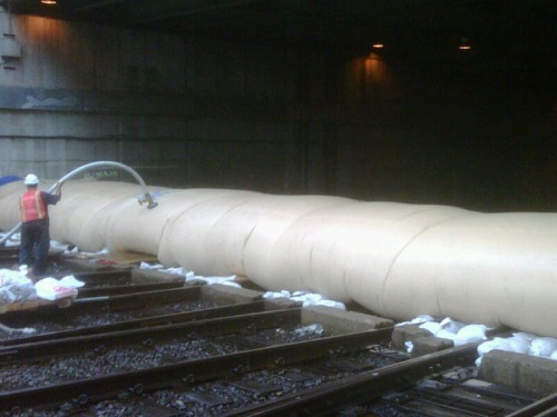 """Hurricane Irene preparation: LIRR employees fill an AquaDam with water to help prevent water from flowing into the LIRR's tunnels to Penn Station."" Apparently all that stands between civilization and water world is a giant tube of water."