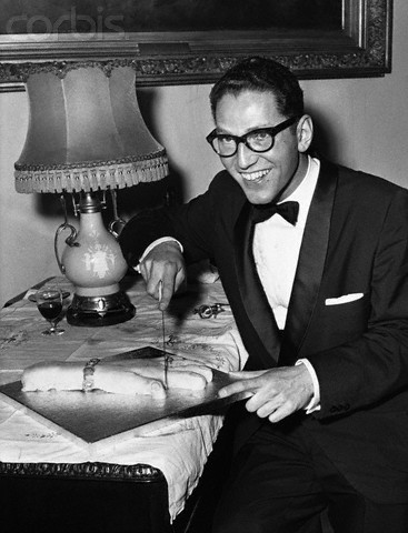 Tom Lehrer cuts into the fingers of a hand-shaped cake during a 1959 visit to London.