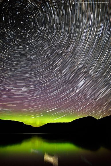 ohscience:    Star trails swirl through candy-colored auroras in a sweet new view of Sugar Lake in British Columbia, Canada, released this week. Taken in July, the long-exposure picture illustrates how stars seem to rotate around what's known as the celestial north pole, an imaginary point in the sky closest to the star Polaris—the dot of light at top left—that seems to intersect Earth's axis of rotation.
