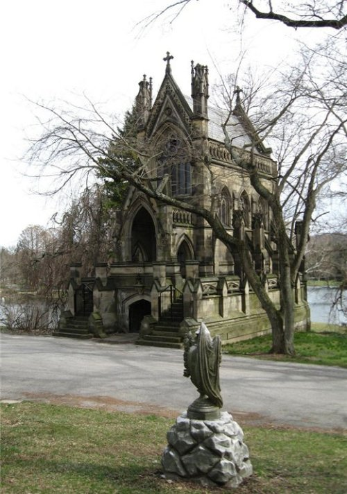 "The Dexter Mausoleum located in section 20 of Spring Grove Cemetery is a private, family mausoleum, often mistaken for one of Spring Grove's three chapels. Dexter was a English immigrant - a ""whiskey baron."" His mausoleum was intended to resemble a Gothic Revival ""funerary monument."" Designed in 1869, it boasts the only two symmetrical buttresses in Cincinnati. It is registered as a historical landmark. If you sit on one of the porch you will see two white, shining dogs run by."