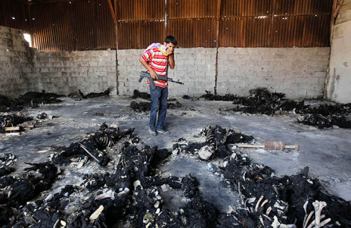 thirdskin:  Tripoli, Libya: a rebel fighter looks at the charred remains of burnt bodies at the Khamis 32 military encampment  Photograph: Louafi Larbi/Reuters
