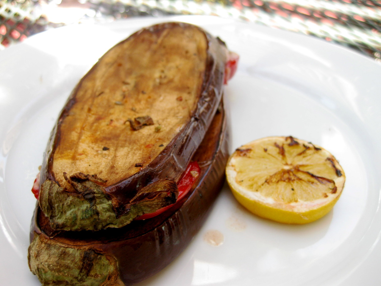 MMMM I love veggie-tastic lunches. This is my grilled Grilled Balsamic Eggplant Basil Sandwich with fresh heirloom tomatoes and a bit of part-skim mozzarella.  Recipe: 1 Eggplant sliced lengthwise 1/4 inch thick (I just grill em all and reserve the extra slices for later) Fresh Basil (as much as you want) 2 slices heirloom tomato  1/4 cup shredded part skim mozerella  1 TBS Balsamic  1 tsp Oregano  Salt and Pepper to taste  Pre-heat the grill. Then I mix the balsamic and oregano and salt and pepper and then I brush the glaze on both sides of the eggplant slices. Then I spray the eggplant with some olive oil pam and put them on the grill on high for about 10 minutes on each side or until I meet my desired softness. Lastly I put the sandwich together by stacking the basil, cheese and tomatoes in between two eggplant slices and then I place the sandwich back on the grill until the cheese is melted. Voila! Healthy veggietasticness.