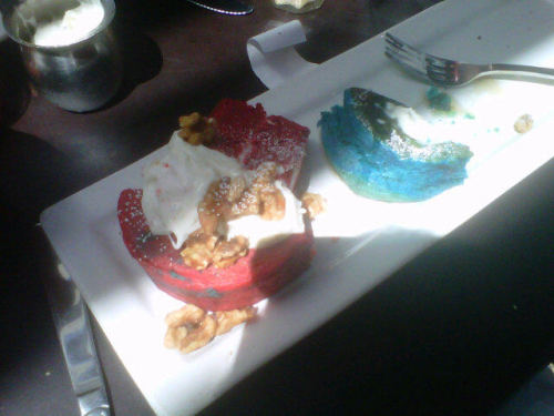THESE ARE RED AND BLUE VELVET PANCAKES FROM LARCHMONT BUNGALOW. pardon the shouting (and the crappy camera phone quality) but this made me really excited. A few friends and I checked Larchmont Bungalow after church today. It's kind of pricey for a college student's budget (almost everything on the menu was $12.95+), but a friend and I split an order of the red and blue velvet pancakes. Perfect because a full order would have been way too much. they were more like cake than pancake and topped with a delicious cream cheese topping. Our other friends enjoyed the burger they split. A nice surprise was the chipotle ketchup served with the fries. The atmosphere of the place was nice. It's a small cafe type place. We sat outside and despite the LA heat today, found ourselves very comfortable. They're dog friendly too, or at least the water bowls they had outside seemed to indicate that they were. It was crowded, but it was brunch time and the food was worth the wait. Next time I go, I would like to try one of their egg dishes. The pancakes were a nice, novel treat, but the orders of eggs benedict that were coming out looked delicious.