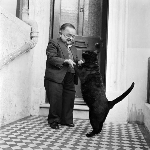 blackandwtf:  Date unknown A little person dances with a black cat. (via Lisa de Torres)