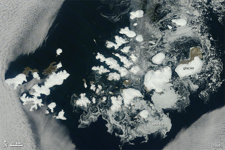 Russia's northernmost territory, Franz Josef Land, is an archipelago of 191 islands in the northeastern Barents Sea. On August 17, 2011, clear skies allowed the Moderate Resolution Imaging Spectroradiometer (MODIS) on NASA's Terra satellite this unobstructed view. Clouds fringe this natural-color scene, like curtains held back from a window. Around the islands, sea ice forms serpentine shapes of light gray and dull white. The glaciers that cap many of the islands are bright white. In ice-free areas, land cover is pale brown, typical of tundra. (via NASA Earth Observatory)