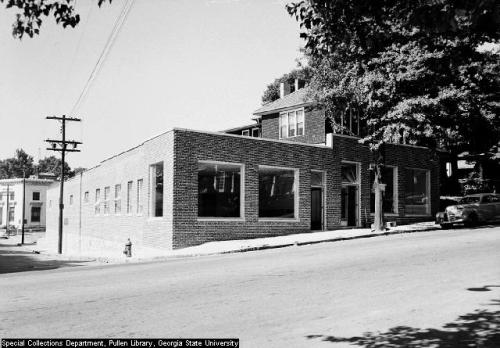 Undated photograph of a commercial building on 11th Street, possibly 1940s.  The cross street is probably Crescent Avenue, as the Southern Bell Telephone building that stood at 10th and Crescent can be seen in the background.  Midtown Atlanta.