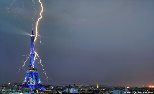 """A lightning strike gives a vivid backdrop to the iconic Eiffel  Tower, while the Paris landmark is illuminated in vibrant blue lights.  Amateur photographer Bertrand Kulik captured the shot which will appear  in an exhibition titled ""Lumieres celestes, lumieres des hommes"", in  Issy L'eveque, Burgundy. It was taken 21:02 GMT, 28 July 2008 during a  storm in the French capital."""