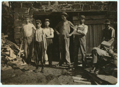 """Group outside Pittman Handle Factory. A fifteen year old boy operating a dangerous boring machine at which he said a boy recently bored half his hand off. To operate this machine (which bores a large hole in the spade handle) the boy has to throw his whole weight onto the lever which pushes the handle (and himself) up against the unprotected borer. A slip might easily result fatally. Boy earns $1.65 a day. This factory has a number of unprotected belts and dangerous machines. One other boy, about the age of this one, was doing all kind[s] of work, taking away the handles from a huge rip saw, etc., and constantly exposed to danger. Pittman Handle Factory, Denison, Tex. Location: Denison, Texas.""  Lewis Wickes Hine September 1913"