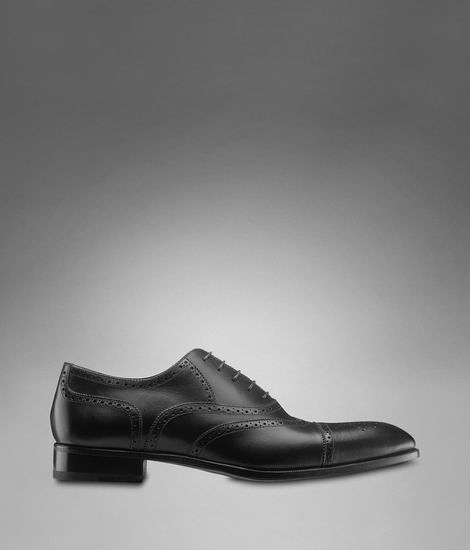 Yves Saint Laurent Eton Lace-up in black leather.As worn by Sherlock for the whole of series 1. Cap toe, richly detailed perforations and expertly crafted leather sole. Italian made.£340 / $550 Available here at ysl.com BONUS FACT: Sherlock's shoes were re-soled with a smaller heel as Benedict Cumberbatch is a lot taller than Martin Freeman already. (Source)