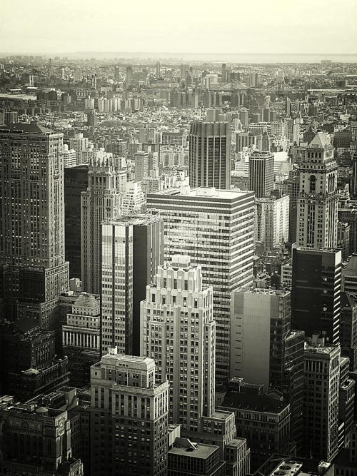 "nythroughthelens:  The New York City skyline featuring the skyscrapers of midtown. New York City. I went to my first photowalk yesterday evening. A large group of around 20 (25?) photographers from Google + got together to walk around Greenwich Village with their cameras. It was a really interesting experience and I ended up meeting a few people I only ever interacted with online prior to the walk. The majority of the photographers were street photographers. Street photography (for those who don't know) is a type of documentary photography that tends to feature subjects in candid situations within public settings. It's not the type of photography I generally gravitate towards (although I have posted a few shots that could fall into that realm). However, what was interesting was that in talking to several of the other photographers, I found that I had a lot of trouble categorizing my own photography. I initially started out by saying that I 'do urban landscapes and some natural landscapes around New York City' but that seemed so vague when I actually said it in conversation! In other conversations, I started to try to explain that I take 'emotive urban' photography which just ended up sounding incredibly pretentious. I also mentioned that I tend to link writing with photography which ended up being more confusing than anything. In actuality, it was quite amusing that I had so much trouble explaining just what it is I 'do'. It's a strange predicament to be in, for sure. I was initially going to write quite a bit of prose to accompany this photo about how the city encompasses the individual leading the individual to seek to rise above the city and some other meandering thoughts about the greater concept of the city in relation to the lone individual. However, the photo discussions from last night have been foremost in my mind. It's sometimes difficult to explain how we focus our passions into tangible form. It could be the reason why humans developed music and art and other creative forms. These forms that exist alongside and sometimes outside of written and spoken language seek to make sense of what often can't be explained with mere words. When I was younger, I used to imagine what a world without written or spoken language would be like. If there were no words to express the complexities and beauty that surrounds us, what would we use to reel in the (often beautiful) chaos? —- I still need to go through the very few photos that I did take on the walk (and maybe share the photos I ended up in as well). I find that when I go out to shoot with people, I am more focused on observing without capturing. I look forward to more walks and more chances to figure out how to put into words that which I can't quite find the words for. —- View this photo larger and on black on my Google Plus page —- Buy ""Looking Out Over The New York City Skyline"" Posters and Prints here, View my store, email me, or ask for help."